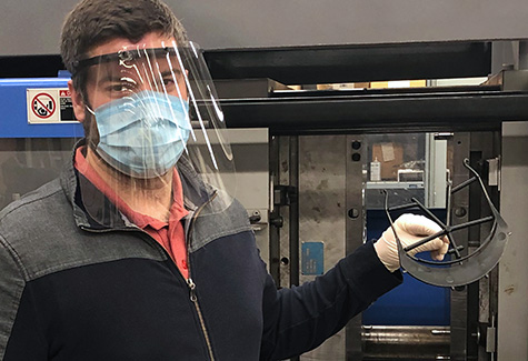 Carlos Castro holds one of the molded visor parts coming out of the injection molding machine in the ISE manufacturing lab